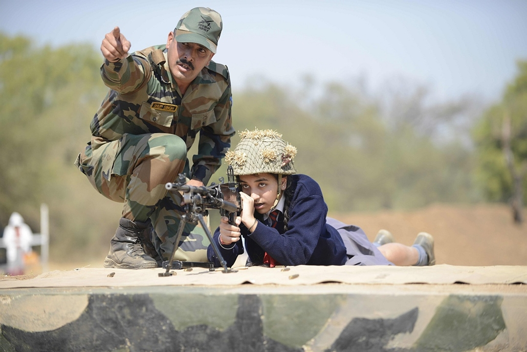 afp. hét képei - 2016.01.25. indiai hadsereg, iskolás géppuskával, An Indian Army soldier helps a schoolgirl as she prepares to fire a Light Machine Gun (LMG) during a demonstration on the eve of Indian Republic Day at the Golden Katar Division Parbat Ali