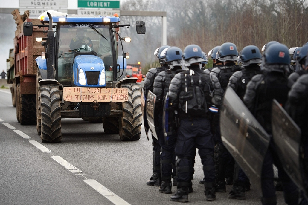 afp. hét képei - 2016.01.25. francia csendőrök, RN 165 autópálya, traktor, tüntetés, French gendarmes stand on the RN 165 motorway facing protesters in a tractor bearing a sign reading Enough with Le Foll klore, help we are dying (in reference to French A