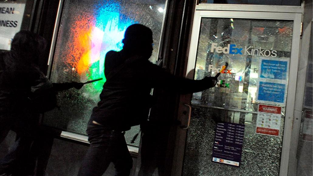 Maszkos tüntető kalapáccsal veri szét egy iroda üvegajtaját a G20-csúcstalálkozó nyitónapján.