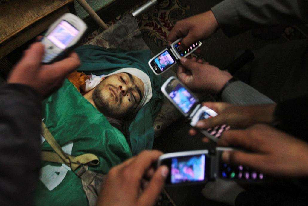 Palesztin gyászolók képeket készítenek egy fiatalról, aki a Hamasz és az izraeli hadsereg közötti összecsapásokban vesztette életét Hebronban, a Gázai övezetben.