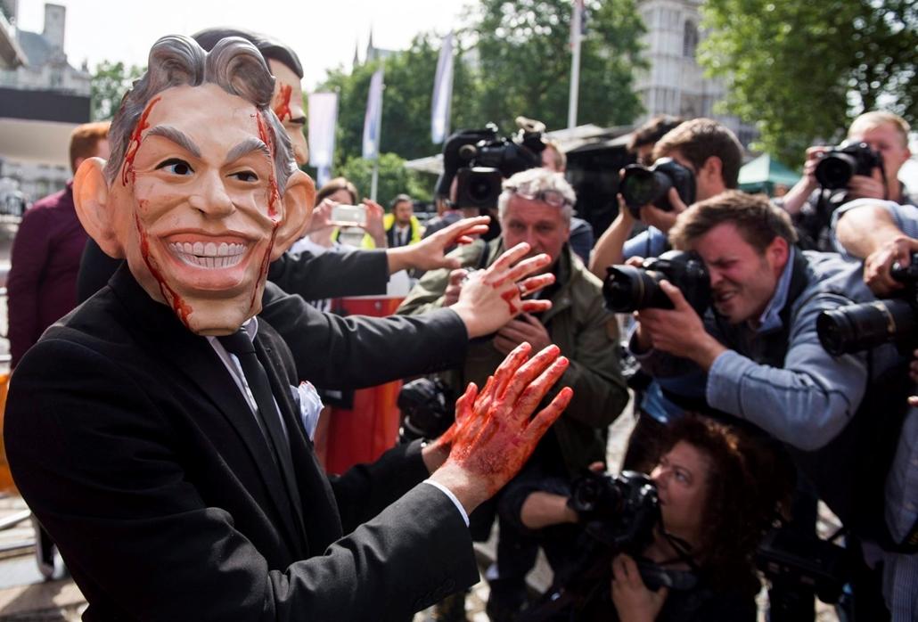 epa.16.07.06. - Tony Blair volt brit miniszterelnököt ábrázoló maszkot viselõ, mûvérrel bekent tiltakozó érkezik a londoni II. Erzsébet Konferencia Központhoz, ahol Sir John Chilcot, a brit diplomáciai szolgálat egykori magas rangú tagja, az iraki háború