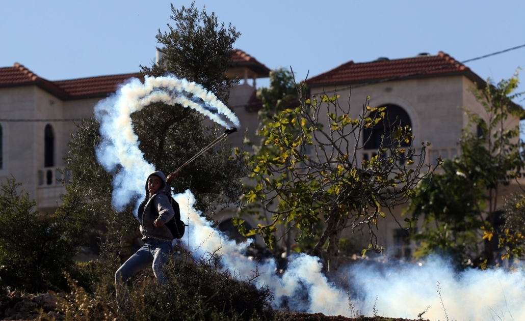 afp. hét képei - BETUNIA, palesztin, füstgránát, 2014.11.06. A Palestinian hurls a smoke grenade back at Israeli soldiers (unseen) during clashes at the entrance of the Israeli Ofer military prison, near the West Bank village of Betunia on November 6, 201