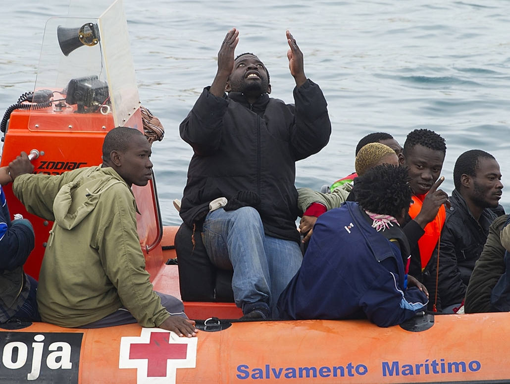 afp. hajóval érkező menekültek, migránsok, - 2012.12.06. A would-be immigrant prays after boarding a boat of the Spanish emergency services in the Strait of Gibraltar, on December 6, 2012. Spanish emergency services intercepted today four inflatable boats
