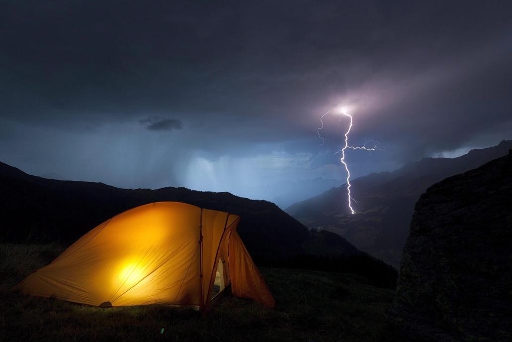 Villámlik a svájci Obersaxen közelében, Graubünden kantonban, amint egy túrázó a sátrában keres menedéket a vihar elől 2012. augusztus 22-én. (MTI/EPA/Arno Balzarini)
