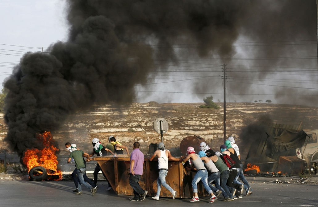 afp. izraeli-palesztin konfliktus 2015 - Ramallah 2015.10.13. palesztin tüntetők konténerrel, Palestinian protesters push a waste container during clashes with Israeli security forces on October 13, 2015 near the Jewish settlement of Beit El, just north o