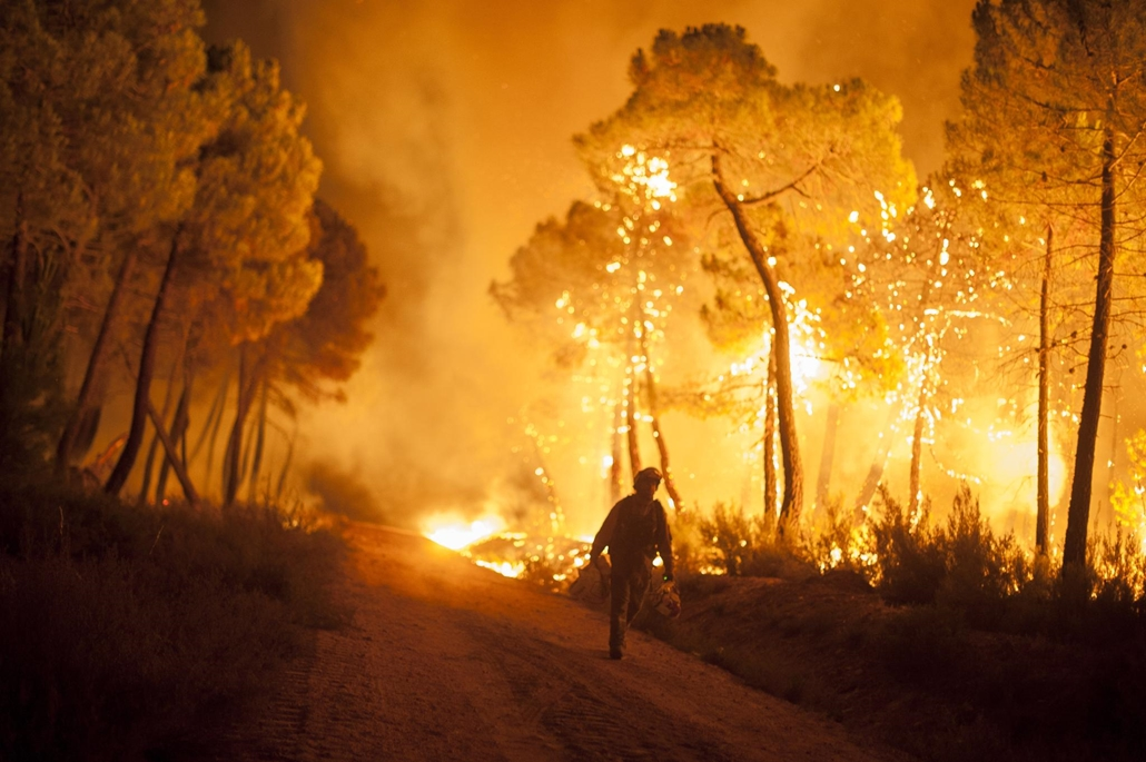 Egy tűzoltó sétál a lángok közt Spanyolországban.
