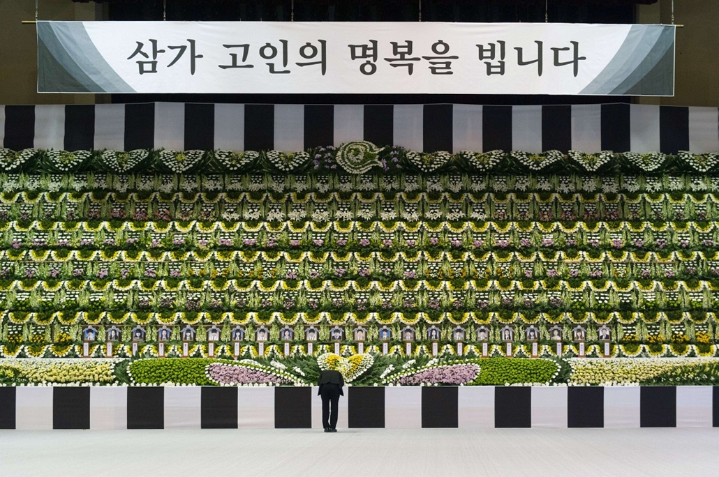 """afp. hét képei - dél-koreai kompbaleset - A mourner (C) bows in front of a newly opened group memorial altar for the victims from the sunken South Korean ferry """"Sewol"""" at the Ansan Olympic memorial hall on April 23, 2014, just down the street from Danwon"""