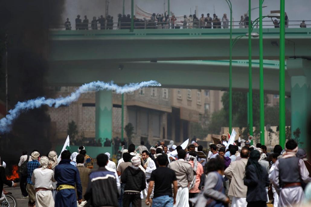 Tüntető dob vissza egy könnygáz-gránátot a rohamrendőrökre Jemenben , arab világ, tüntetések, mohammed próféta