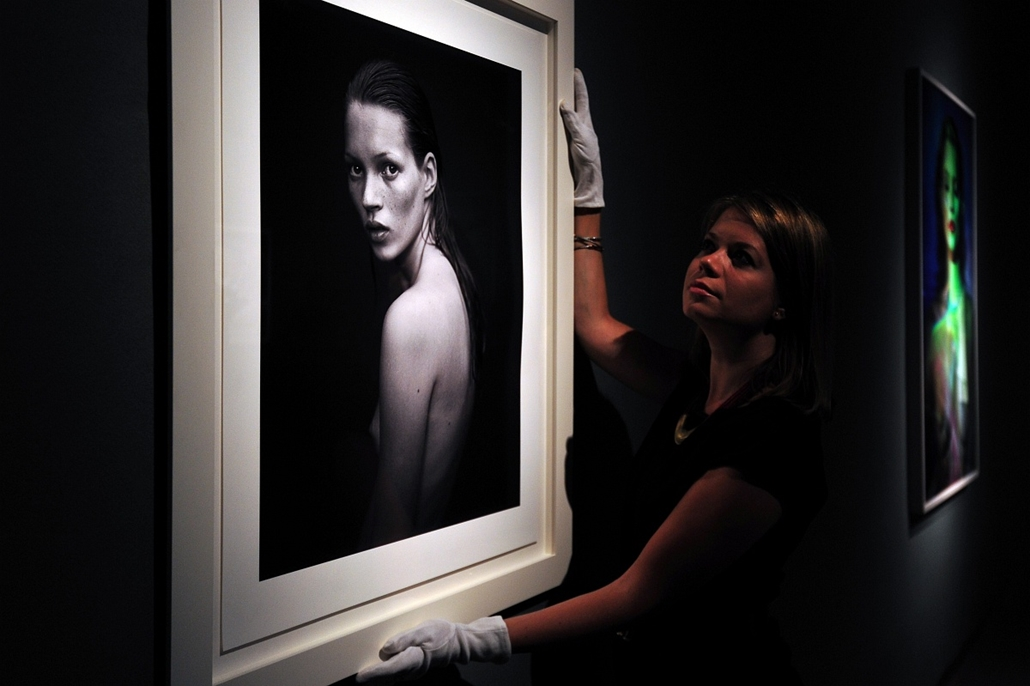afp. Kate Moss szupermodell 40 éves - nagyítás - 2013.09.04. London An auction house employee poses with a photograph of British model Kate Moss taken by Mario Sorrenti for the Calvin Klein Obsession campaign at Christie's auction house in central London