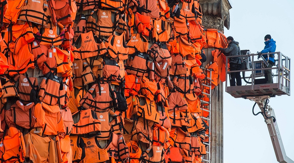 afp. 66. Berlini Nemzetközi Filmfesztiválon, Berlinale 2016 - Assistants of Chinese artist Ai Wei Wei decorate the columns of Berlin's Konzerthaus with lifejackets, on February 13, 2016, as part of an installation intended to remind people of the ongoing
