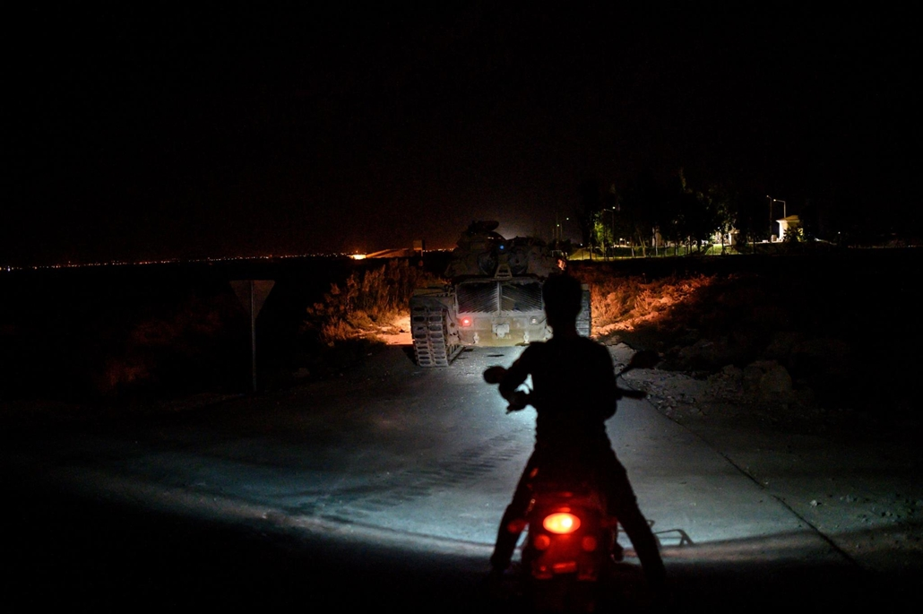 afp.19.10.08. A man steers his moped as a Turkish army's tank drives towards the border with Syria near Akcakale in Sanliurfa province on October 8, 2019. - Turkey said on October 8, 2019, it was ready for an offensive into northern Syria, while President