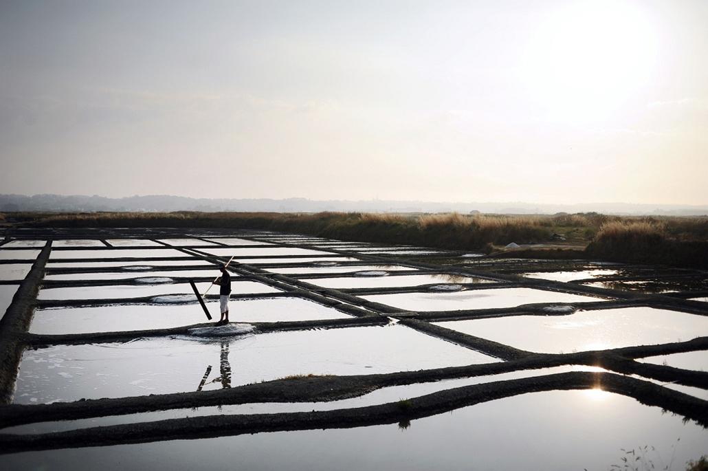 afp. hét képe 0623-0628 - Guérande, Franciaország 2014.06.24. This picture taken on June 24, 2014 in Guerande, western France, shows Guillaume Baholet, a salt worker, harvesting salt at the salt plant Les salines de Guerande. About 200 salt workers harves