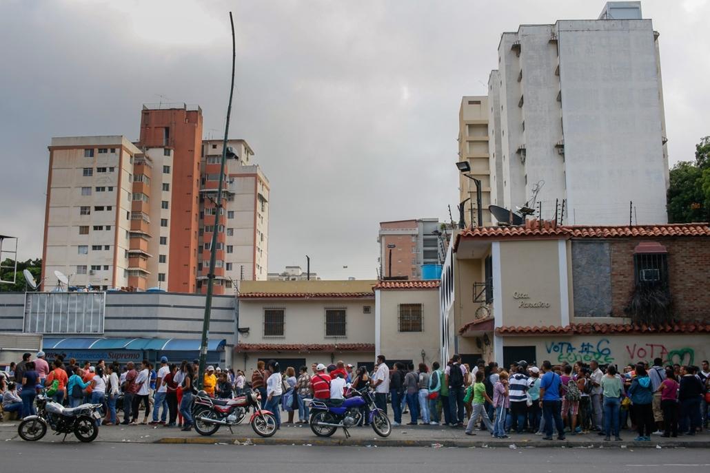 afp.16.03.02. - Alapvető élelmiszerekért állnak sorba emberek rendőri felügyelettel egy caracasi bevásárlóközpont előtt 2016. június 1-jén. Az élelmiszer és más árucikkek jegyrendszer alapján történő elosztását lehetővé tévő gazdasági szükségállapot januá