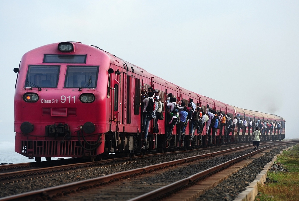 afp. nagyítás - hét képei - Colombo, Srí Lanka, vonat, utazás 2014.05.26. Sri Lankans hold on to the sides of passenger train in Colombo on May 26, 2014. Train travel is a popular mode of transport in this nation of 20 million people, due to its affordabi