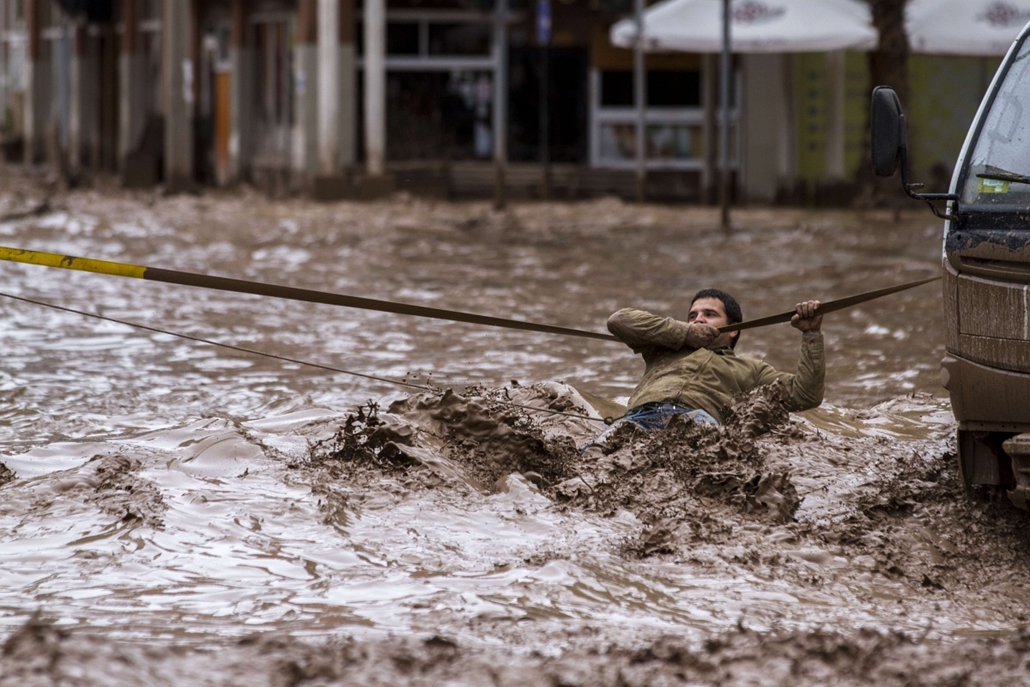 afp. árvíz chilében, 2015.03.26. Copiapó, A man clings to a security line to cross a street flooded by the overflowing of the Copiapo River due to heavy rainfall that affected some areas in the city, in Copiapo, Chile on March 26, 2015. Flash floods in a