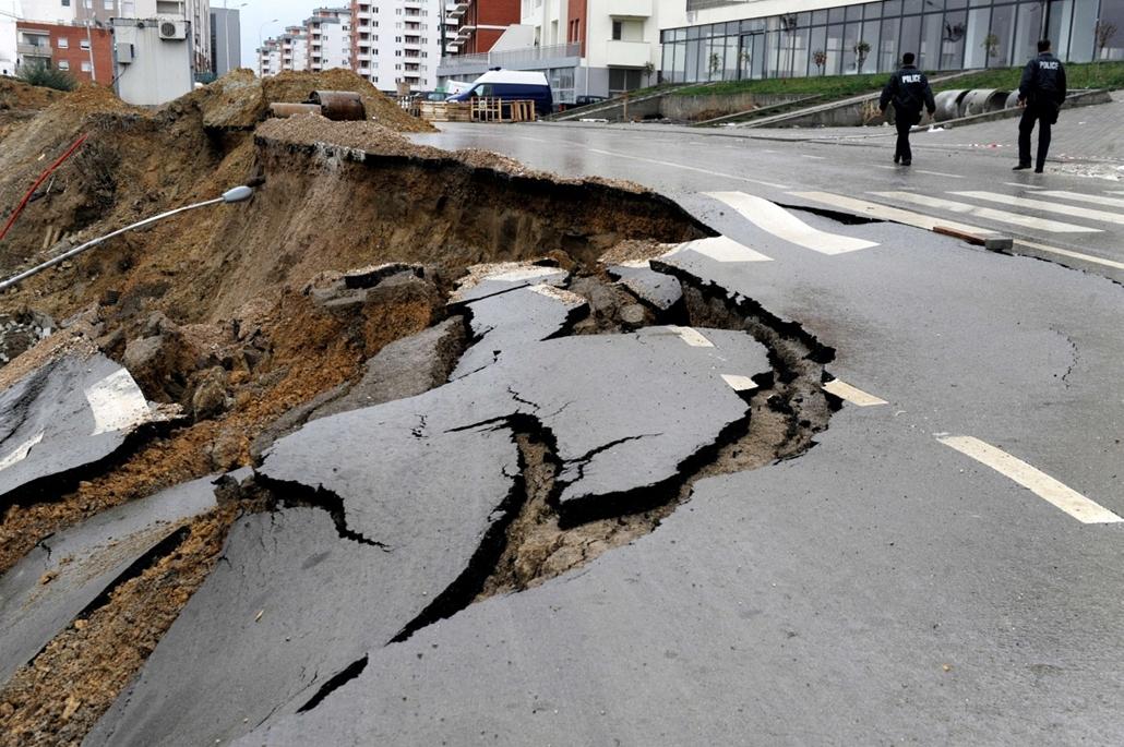 a hét képe nagyítás-fotógaléria kép - Kosovar policemen walk past a damaged street after a landslide in Pristina due to heavy rains on September 30, 2013.
