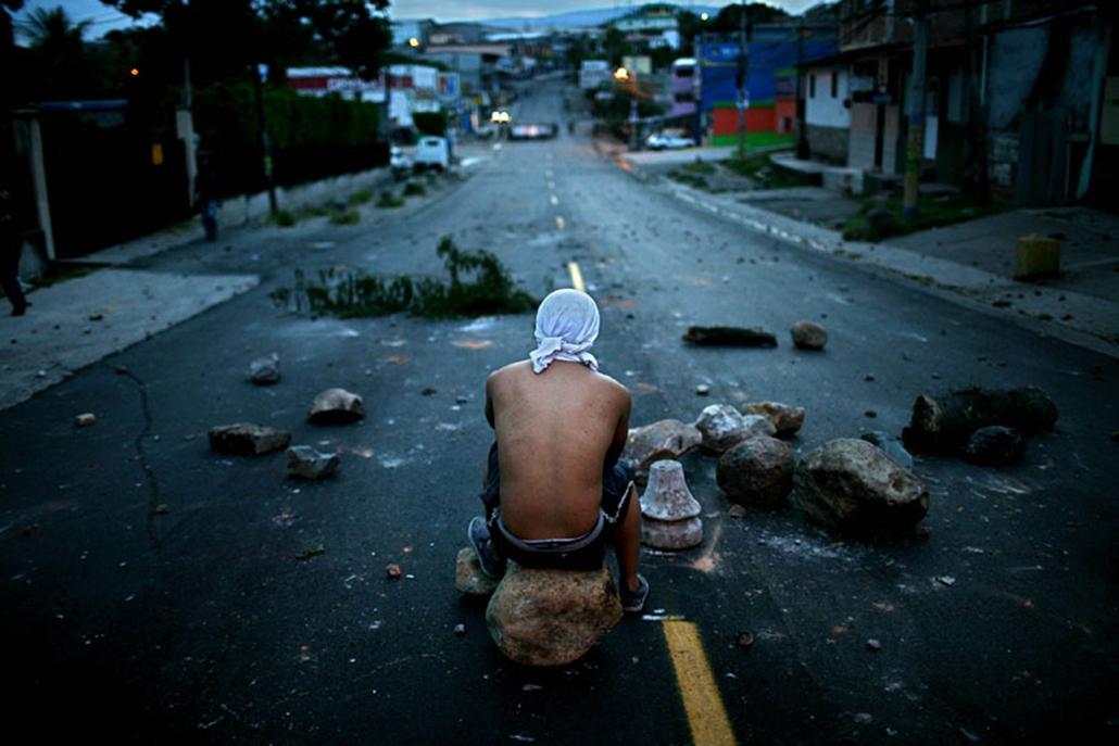 Az úttorlasz egyik sziklakövén ül Manuel Zekaya államcsínnyel megbuktatott és emigrációba kényszerített hondurasi elnök egyik támogatója Tegucigalpában. Előző nap Zelaya váratlanul visszatért hazájába, hogy visszaállítsa a demokráciát.Jelenleg a brazil nagykövetségen tartózkodik.