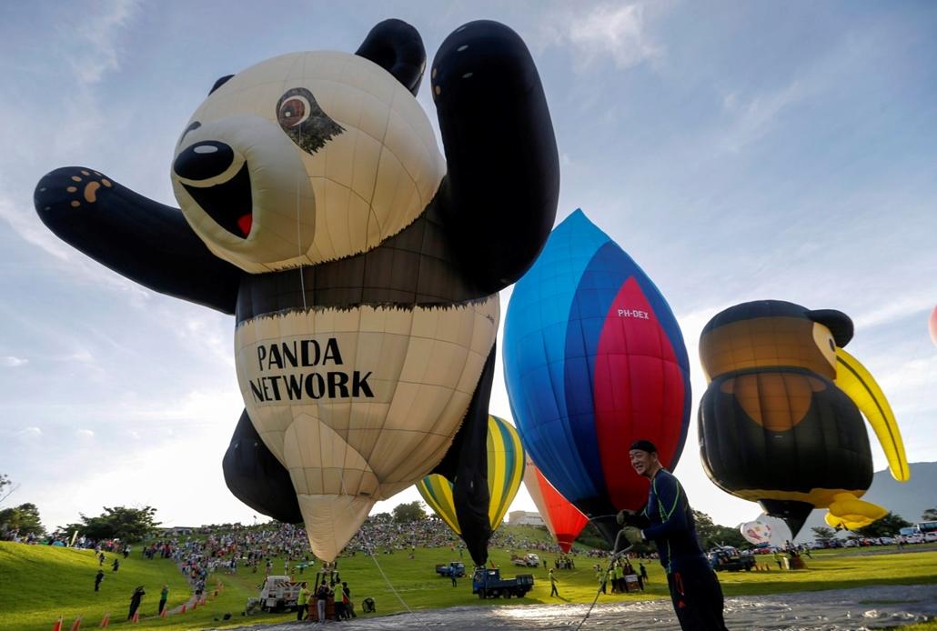 epa.16.07.01. - Felszállni készülõ japán résztvevõ kezében a hõlégballonja kötelével a délkelet-tajvani Tajtungban rendezett nemzetközi hõlégballon fesztivál kezdetén, 2016. július 1-jén. Idén tizennégy országból összesen harmincegy csapat vesz részt a jú