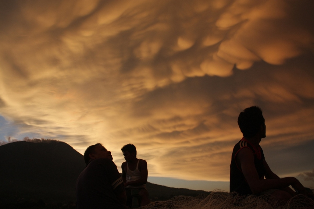vulkán, tűzhányó - 2011-12-11 INDONESIA, TERNATE : This photograph taken on December 11, 2011 shows residents travelling on a boat looking at a dramatic cloud formation during sunset near the erupting Mount Gamalana volcano on the island of Ternate. The v
