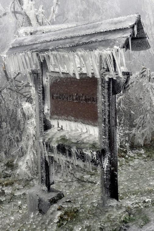 mti. ónos eső, jegesedés, tél 2014, 2014.12.02. Pilisszentkereszt,Jég borítja a településről távozókat köszöntő táblát a Dobogókőre vezető úton 2014. december 2-án. A katasztrófavédelem és a rendőrség lezárta az utat az ónos esőtől kialakult eljegesedés m