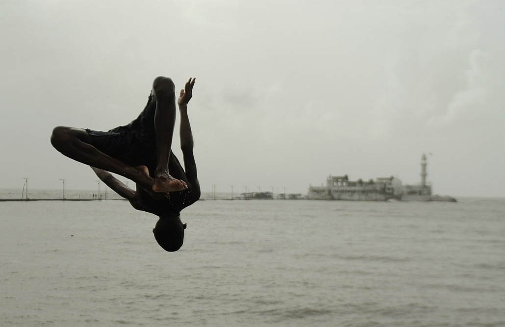 afp. a hét képei 0616-0621 - Mumbai, India 2014.06.17. An Indian youth jumps into Arabian Sea near the Haji Ali mosque in Mumbai on June 17, 2014. The India Meteorological Department (IMD) has declared the start of the monsoon season, predicting below-ave
