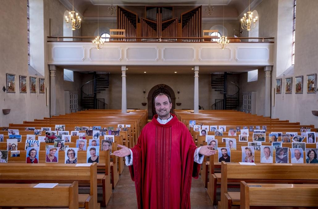 nagyítás - !AP! 20.05.08ig! mti.20.04.04. Christian Rauch katolikus pap a hívők képeivel a padokban, mielőtt misét tart, amelyről videófelvétel készül a németországi Lampertheim Szent András-templomában 2020. április 4-én. A koronavírus-járvány miatt nem