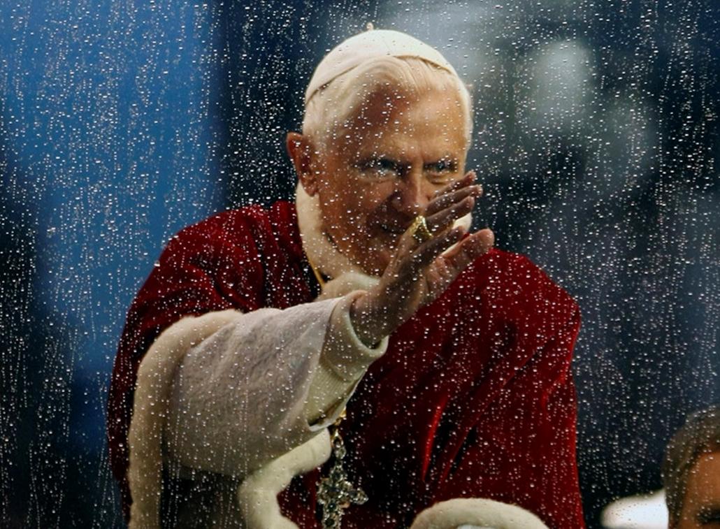 XVI. Benedek a pápamobilból integet a tömegnek Rómában.