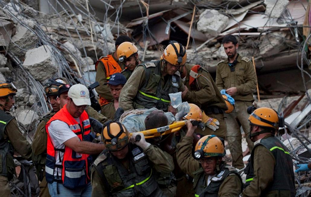 Romok alól kimentett túlélőt visznek izraeli mentők Port-au-Prince-ben 2010. január 16-án, miután négy nappal korábban a Richter-skála szerinti 7-es erősségű földrengés rázta meg Haitit. Az egészségügyi világszervezet, a WHO becslése szerint a földmozgás következtében 40-50 ezer ember vesztette életét a karibi szigetországban.