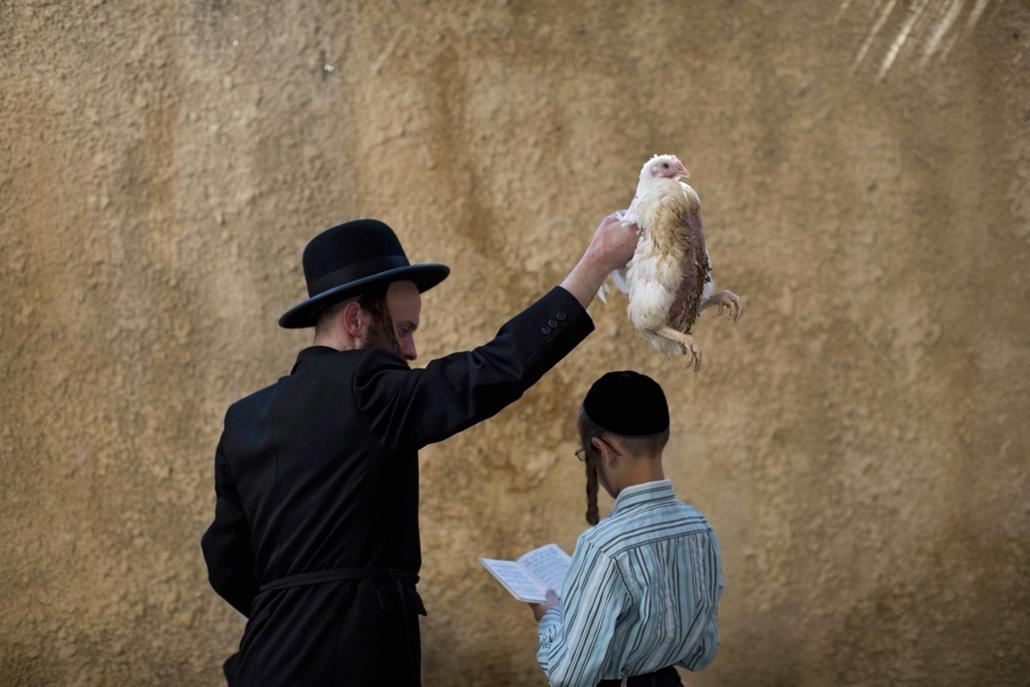 epa. Izrael - Vallás, Jeruzsálem, 2014.10.02. Ultraortodox zsidó férfi egy csirkét forgat egy fiú feje fölött és imádkozik a kaparot (vezeklés) ceremóniája közben Jeruzsálemben 2014. október 2-án, egy nappal a jóm kipúr, a bűnök engesztelésének ünnepe elő