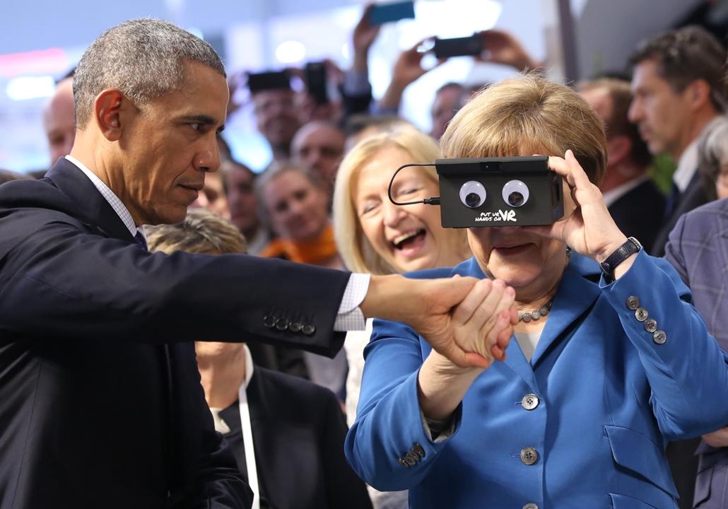 hét képei - afp.16.04.25. - Hannover: Barack Obama amerikai elnök (b) Angela Merkel német kancellár kezét fogja, miközben Merkel kipróbál egy virtuális valóság (VR) szemüveget a Hannoveri Vásáron 2016. április 25-én. Obama kétnapos látogatáson tartózkodik