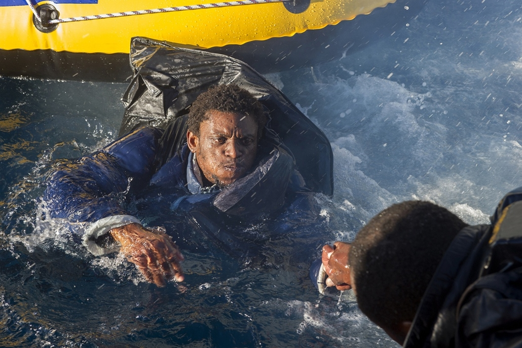 afp. hajóval érkező menekültek, migránsok, - 2012.12.03. A would-be immigrant is helped to get on board a Spanish emergency services (Salvamento Maritimo) boat off the Spanish coast, on December 3, 2012. Spanish emergency services and the Moroccan navy in