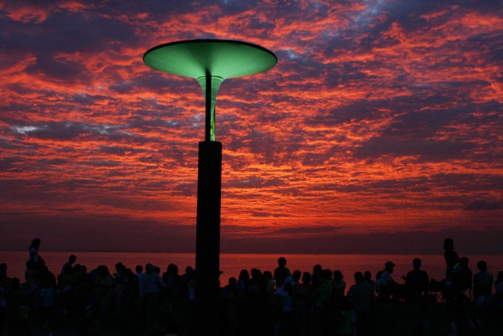 A maniliai tengerparton gyűlnek össze emberek, hogy a naplementében gyönyörködjenek.