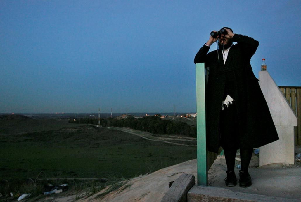 Izraeli telepes a Gázai övezetben dúló harcokat nézi.