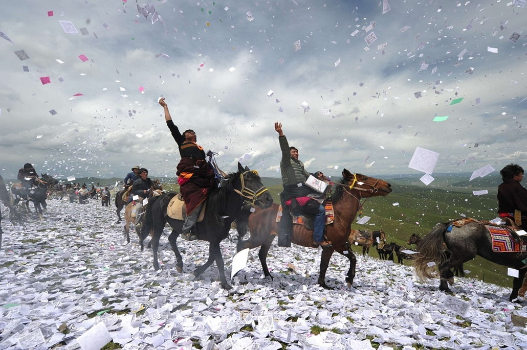 """afp. a hét képei 0616-0621 - 2014.06.18. This picture taken on June 18, 2014 shows Tibetans throwing """"longda"""", pieces of prayer paper,  into the air as they gather to celebrate the wei sang festival, in Hongyuan of Aba town, southwest China's Sichuan prov"""