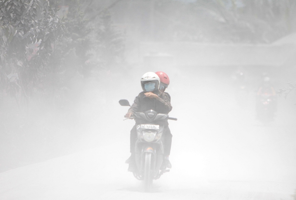 vulkán, tűzhányó - 2013-11-09 INDONESIA, Karo : Indonesian motorists wear masks while passing through an area covered by thick ash as Sinabung volcano continues spewing volcanic materials and thick smoke into the air in Karo on November 9, 2013. About 1,7