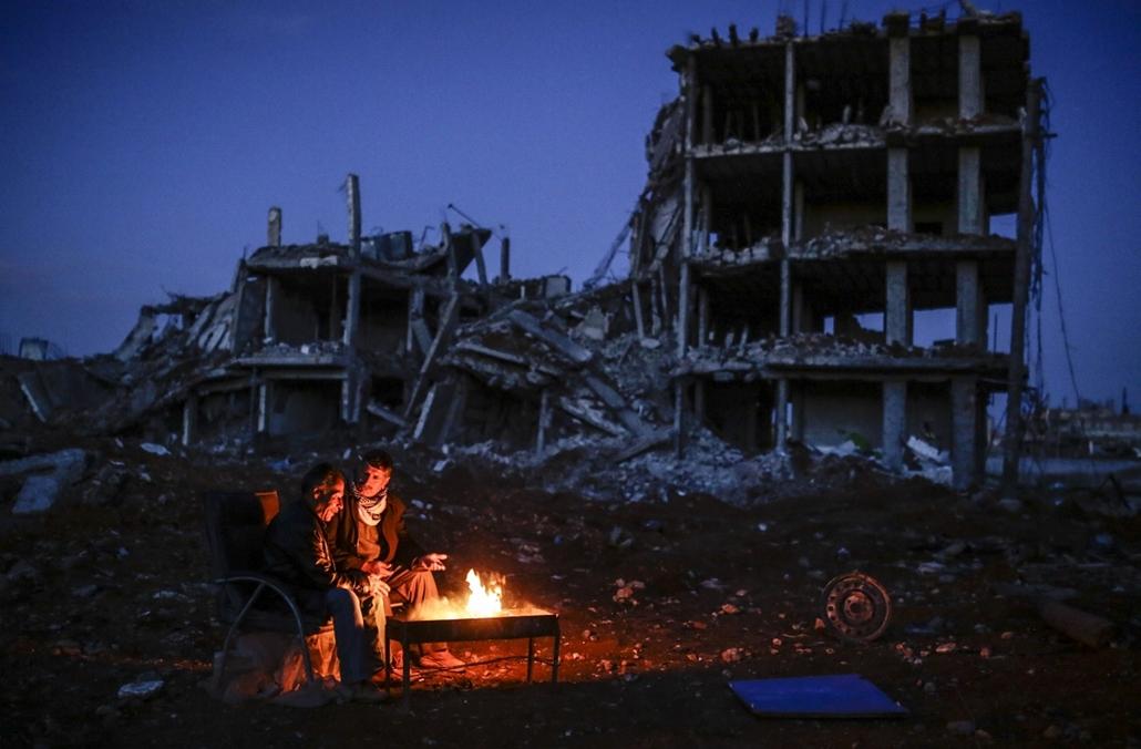afp. hét képei - 2015.03.22. Kobane, Szíria, Kurd férfiak ülnek,  tábortűz - Kurdish men sit near bonfire near a destroyed building, in the Syrian Kurdish town of Kobane, also known as Ain al-Arab, on March 22, 2015.