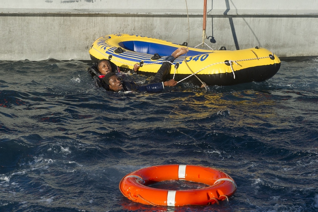 afp. hajóval érkező menekültek, migránsok, - 2012.12.02. Would-be immigrants grab the ropes of an inflatable boat before being rescued by Spanish emergency services and the Moroccan navy off the Spanish coast, on December 2, 2012. Spanish emergency servic