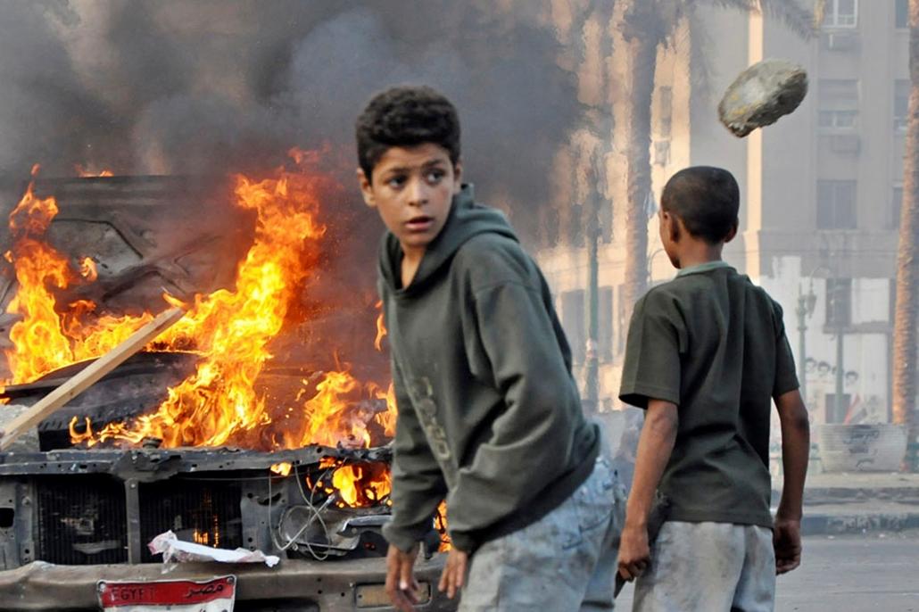 Fiatalok gyülekeznek egy égő kocsi mellett Kairóban , arab világ, tüntetések, mohammed próféta