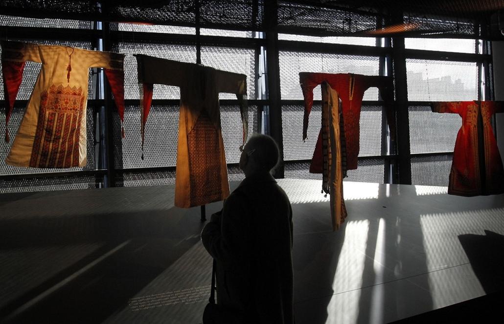 Franciaország - szír népviseletet vizsgáló nő a ''Women in Orient'' kiállításon a párizsi Quai Branly Múzeumban.