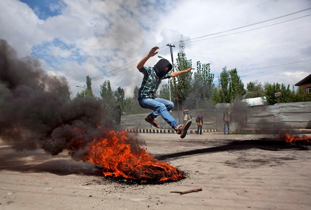 Tüntető ugrik át egy égő gumin Kasmírban , arab világ, tüntetések, mohammed próféta