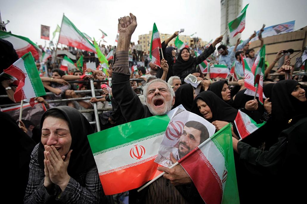 Az újraválasztott Mahmúd Ahmadinezsád iráni elnök támogatói hallgatják Ahmadinezsád beszédét Teheránban, két nappal az iráni elnökválasztás után.