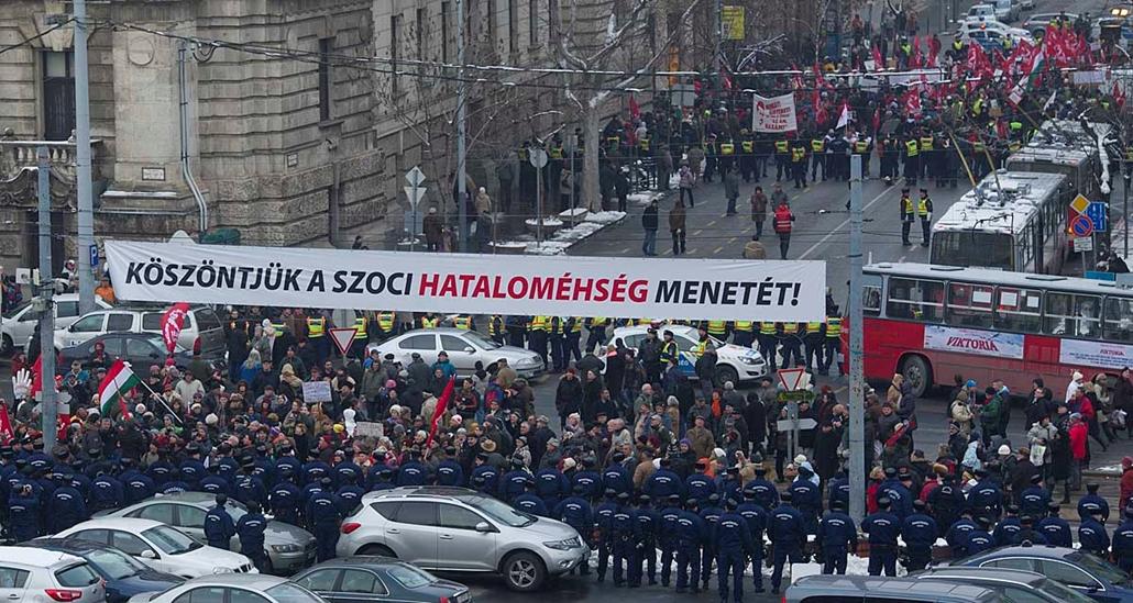 Az éhségmenet a Kossuth térre ér, kormánypárti transzparens az Alkotmány utcával szemben, parlament ablakából nézve