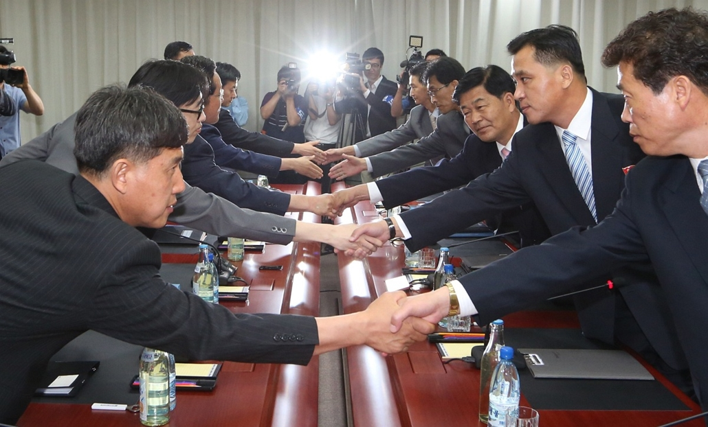 afp. hét képe 0623-0628 - Kaesong, Dél-Korea, 2014.06.26. This handout photo taken and released on June 26, 2014 by the Unification Ministry of South Korea shows members of South Korea's Unification Ministry (L) shaking hands with their North Korean count