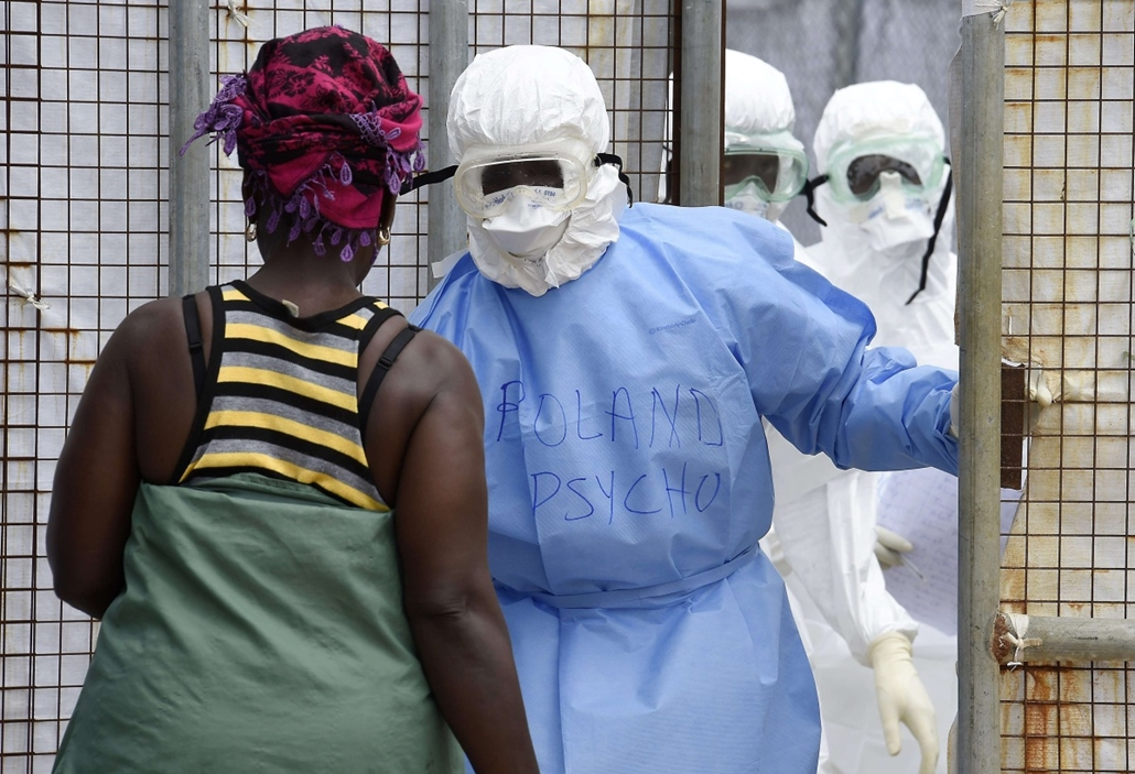 afp. hét képe - Monrovia, Libéria, 2014.09.30. Health workers in protective suits greet a woman who has come to deliver food to relatives at Island Hospital where people suffering from the Ebola virus are being treated in Monrovia on September 30, 2014. L