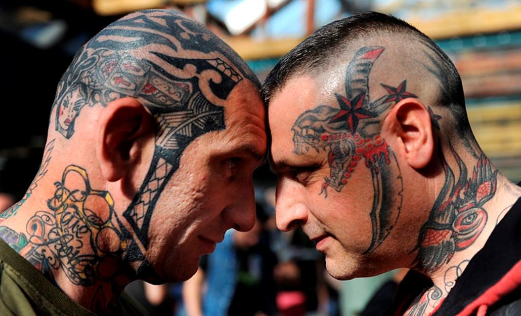 Tetoválóművészek alkotásait a testükön viselő férfiak fényképezkednek Londonban, amikor megkezdődik a tetoválóművészek háromnapos világtalálkozója.