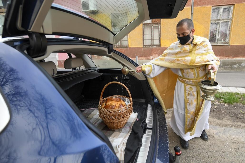 mti.21.04.04. Görögkatolikus pap megszenteli a húsvéti ételeket a hajdúdorogi görögkatolikus székesegyház előtt lévő közúton 2021. április 4-én. A koronavírus-járvány miatt idén a hívek a kocsijaikban hagyták a megszentelésre szánt ételeket és a pap ott s