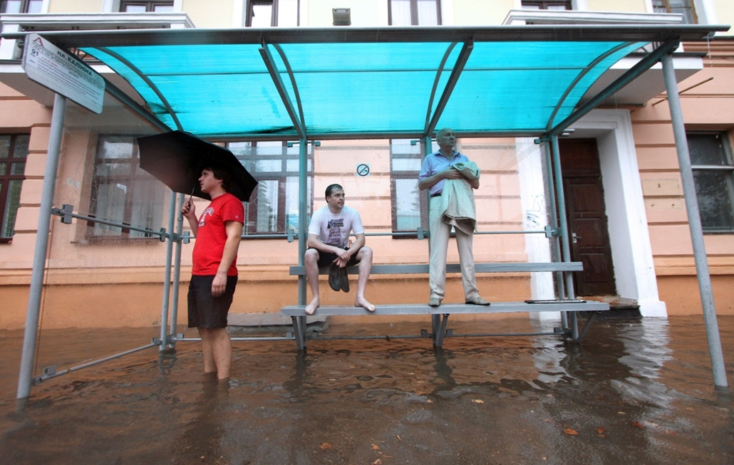 afp. hét képei 0811-0816 - Minsk, BELARUS People wait for the bus in a flooded bus stop during heavy rain in Minsk, on August 12, 2014