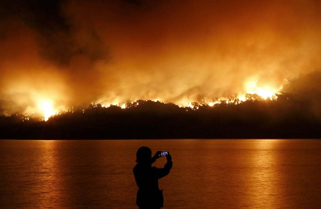 afp. hét képei - Futalaufquen, Argentína, 2015.03.24. tűz a nemzeti parkban, A woman takes pictures of the wild fires raging through Los Alerces National Park, near the Futalaufquen village, in the Patagonian province of Chubut,, some 1900 Km southwest of