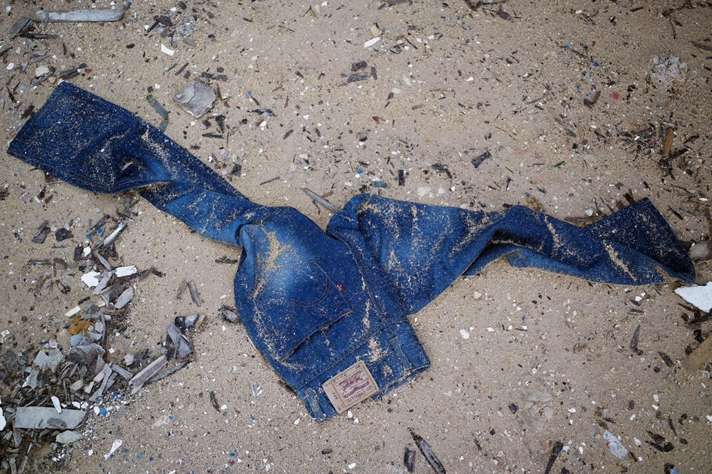 afp. hajóval érkező menekültek, migránsok, - 2013.10.08. A pair of jeans is pictured on October 8, 2013 in the sand near a boat junk yard where are kept boats used by immigrants to sail to Lampedusa near the port of the Italian island. Divers in Italy res