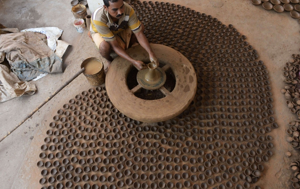 afp. hét képei - Hyderabad, India, 2014.10.15. indiai Fazekas - An Indian potter makes earthenware oil pots or 'diyas' ahead of the forthcoming Diwali festival on the outskirts of Hyderabad on October 15, 2014. Diyas, which are lit and placed around the h